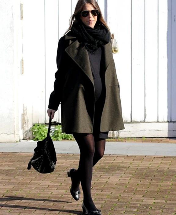 dark haired girl, pregnant, wearing sunglasses, black midi dress, black scarf, army green coat, black stockings, low-heeled shoes and black handbag