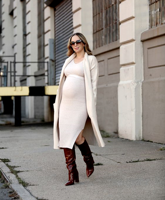 pregnant blonde girl, with sunglasses, long beige knitted dress, long beige coat, long red leather high-heeled boots