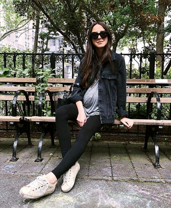 pregnant long hair girl wearing sunglasses, gray top, black denim jacket, black leggings, beige sneakers