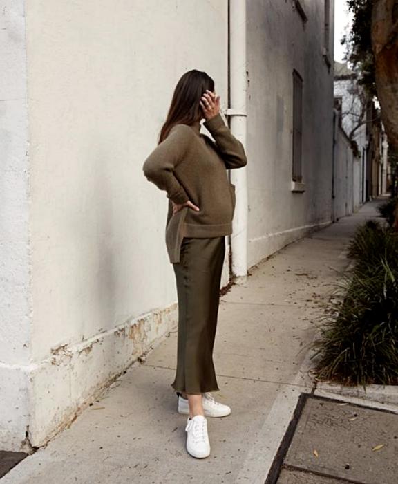 pregnant long hair girl wearing dark green oversized sweater dark green satin skirt and white low top sneakers