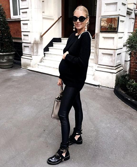 pregnant blonde girl wearing sunglasses, black oversized sweater, black leather leggings, black ankle boots and beige handbag