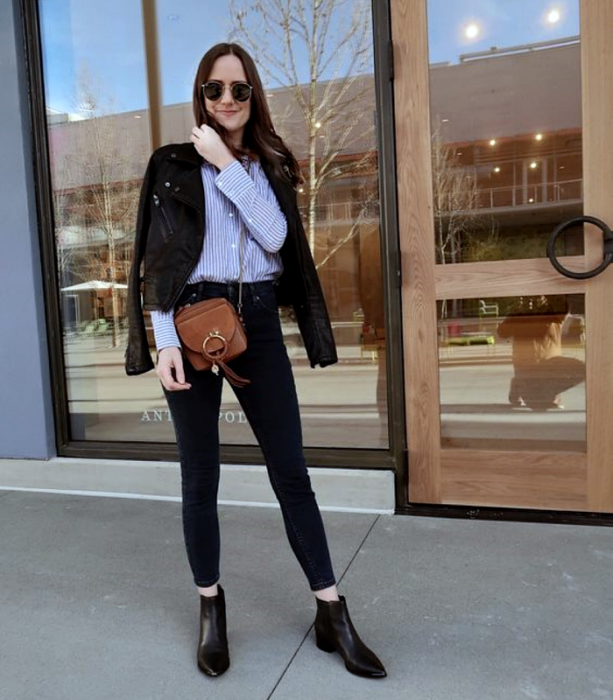 brown haired girl wearing sunglasses, blue white striped shirt, leather jacket, black skinny jeans, black high heel ankle boots and brown bag