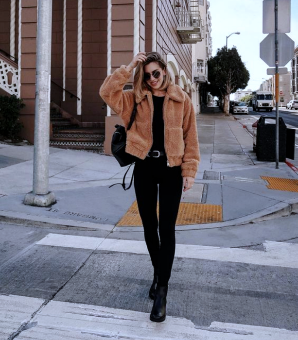 light haired girl wearing sunglasses, brown teddy coat, black t-shirt, black skinny jeans, black high heel ankle boots, black backpack