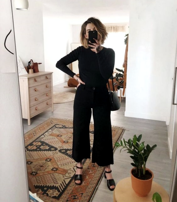 light short hair girl wearing black long sleeve t-shirt, black flared jeans, black heeled sandals and black handbag