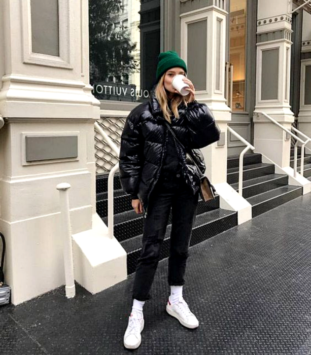 blonde haired girl wearing green beanie, black puffer jacket, black skinny jeans, white sneakers and black bag with coffee