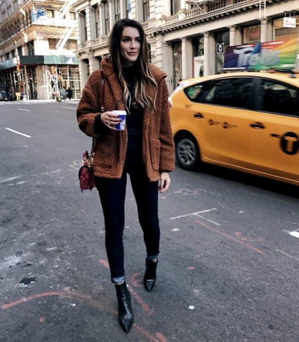 brown haired girl wearing black turtleneck top, brown teddy coat, black skinny jeans, black heeled ankle boots and mini brown bag