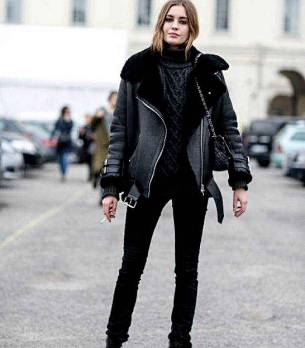 chica rubia usando un suéter tejido gris, chamarra de cuero negra, skinny jeans negros, bolso negro de piel