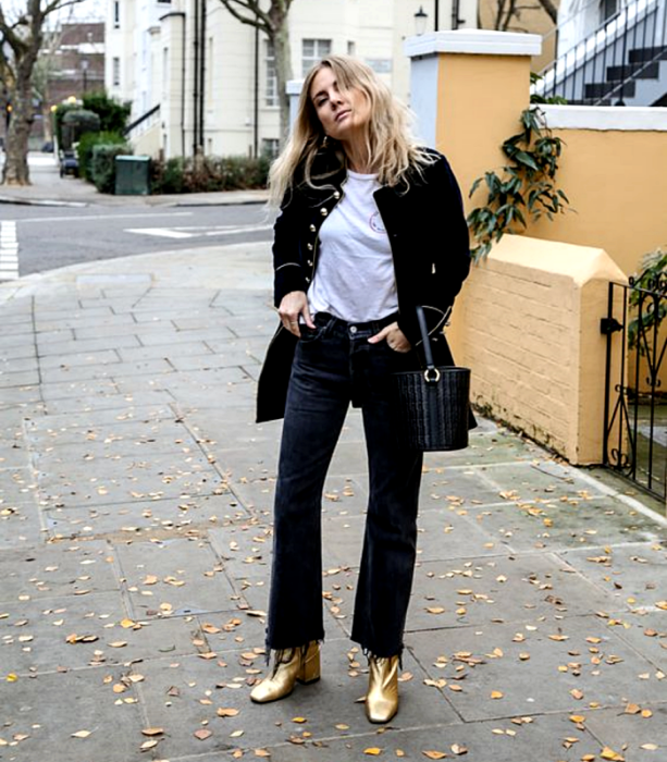blonde girl wearing a white t-shirt, long black jacket, black flared jeans, golden high heel ankle boots and black bucket bag