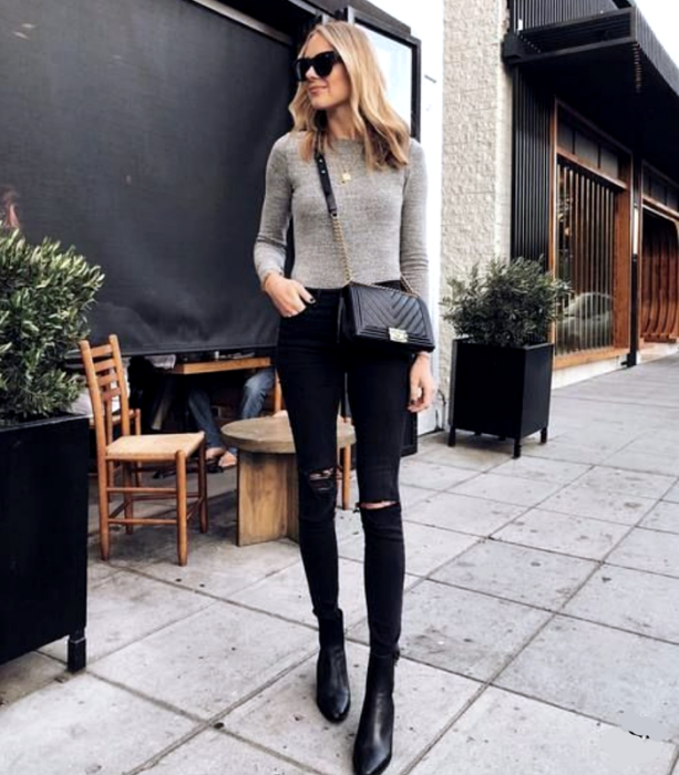 blonde girl wearing sunglasses, beige sweater, black skinny jeans, black leather ankle boots, black handbag