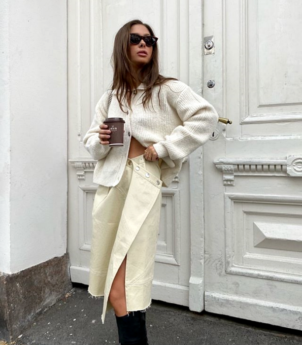 brown haired girl wearing sunglasses, white oversized cardigan, beige leather skirt, black long boots
