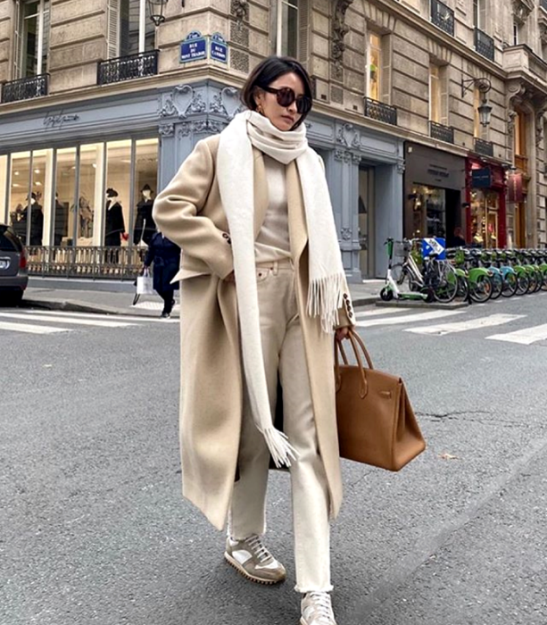 brown-haired girl wearing sunglasses, white scarf, white top, long beige coat, white pants, beige sneakers, light brown leather bag