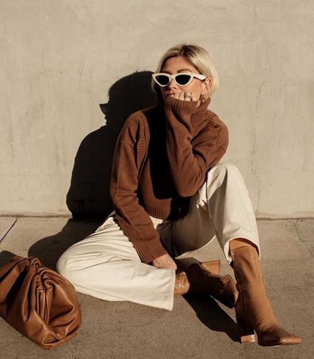 blonde girl wearing white sunglasses, brown sweater, beige pants, light brown leather ankle boots, brown handbag