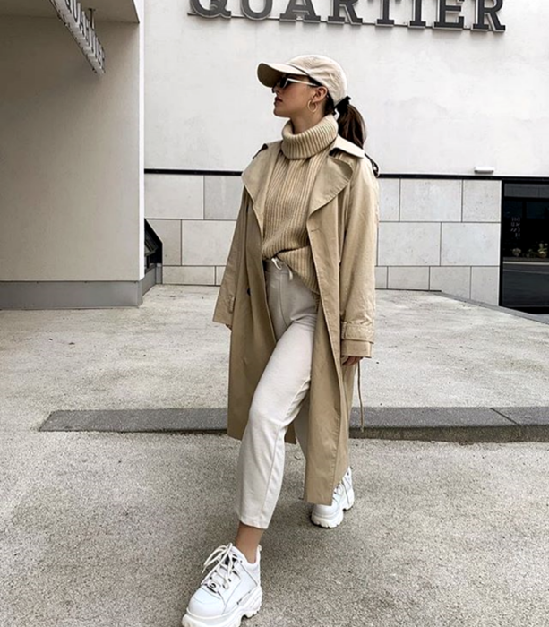 brown-haired girl wearing beige cap, beige turtleneck knitted sweater, long beige coat, beige dress pants, white sports sneakers