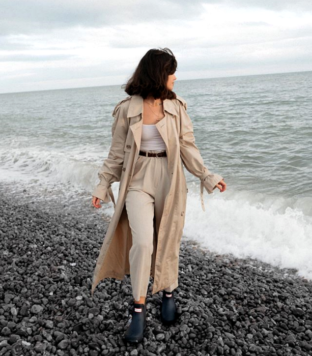 dark haired girl wearing long beige coat, white top, black belt, beige dress pants, black rain booties