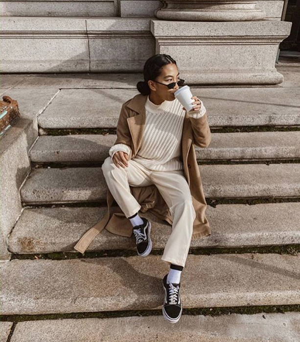 brunette girl wearing sunglasses, beige knitted sweater, long brown coat, beige pants, black vans with white lines