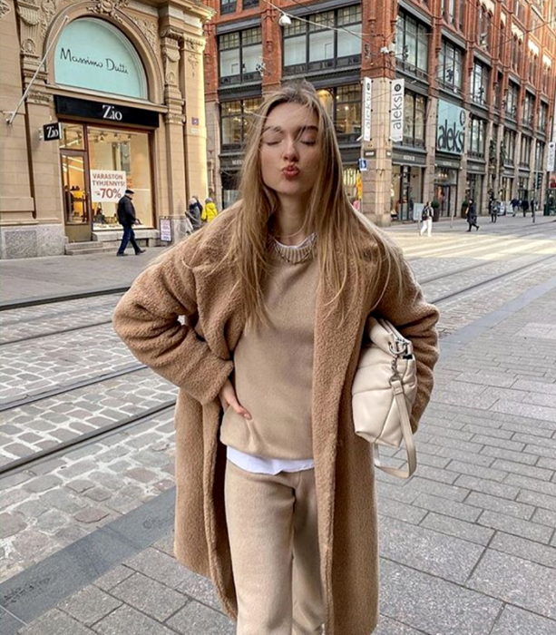 blonde girl wearing beige sweater, light brown teddy coat, white top underneath, beige pants and beige handbag