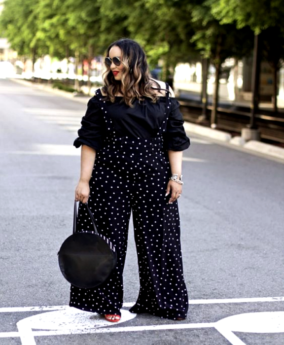 light haired curvy girl wearing sunglasses, 3/4 sleeve off shoulder top, black white polka dot jumpsuit and suspenders, round black clutch bag and red high heel sandals
