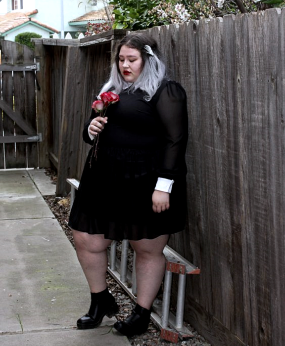 gray haired curvy girl wearing long sleeve black dress and white cuffs, semitransparent black tights and black high heel ankle boots