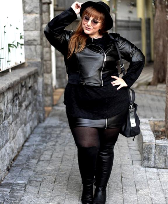 curvy redhead girl wearing black hat, sunglasses, black leather jacket, long black top, black mini skirt, black stockings, black long heeled boots and black handbag