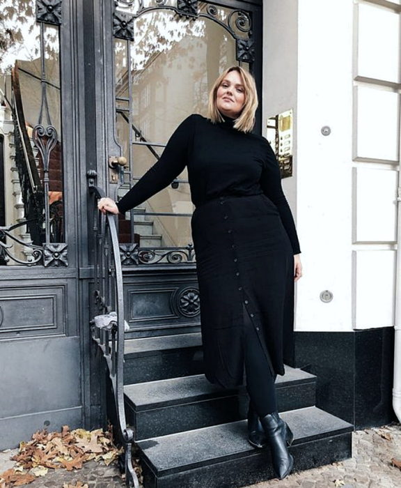 short blonde hair curvy girl wearing black long sleeve turtleneck sweater, black button up maxi skirt, black opaque tights, black leather ankle boots