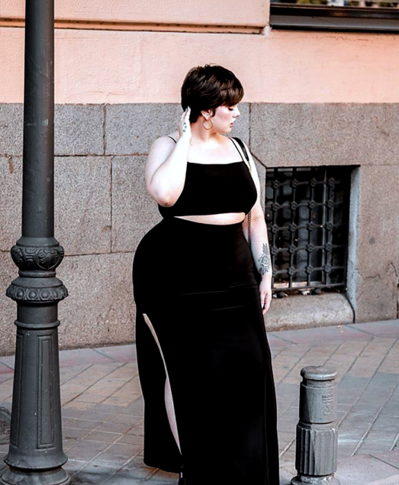 curvy girl with short black hair, wearing a black crop top with thin straps, black maxi skirt with leg slit and black handbag