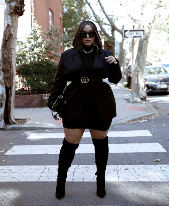 short brown hair brunette curvy girl wearing sunglasses, black high neck top, black oversized blazer, black belt with gold buckle, black long boots, black clutch bag