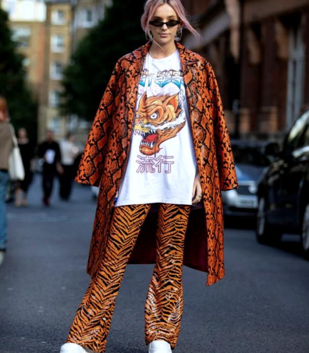 chica rubia usando lentes de sol, camiseta blanca oversized con estampado de dragon, abrigo largo de cuero naranja con líneas negras, pantalones de cuero acampanados color naranja con animal print de tigre y tenis blancos