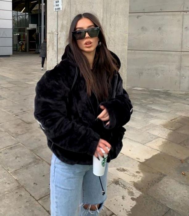 chica de cabello largo usando lentes de sol, abrigo oversized negro afelpado, jeans holgados