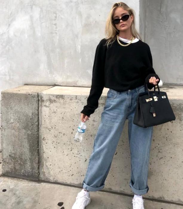 chica rubia usando lentes de sol, sudadera negra, camiseta blanca, jeans holgados y tenis blancos,  bolso  negro de mano