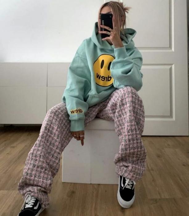 chica rubia usando una sudadera oversized azul celeste con estampado de carita feliz amarilla, pantalones holgados rosas con cuadros grises y tenis negros vans