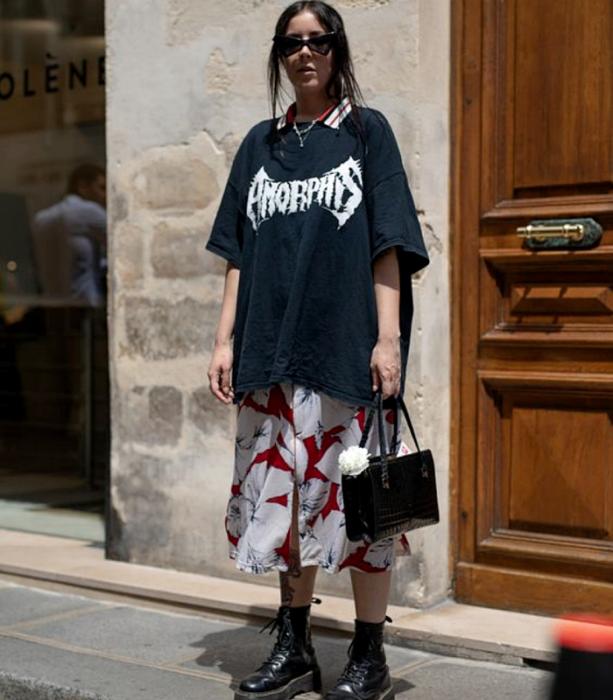 chica de cabello oscuro usando lentes de sol, camiseta oversized azul marino con estampado blanco, vestido blanco largo de flores blancas con rojo, botas negras de suela gruesa y bolso negro de mano