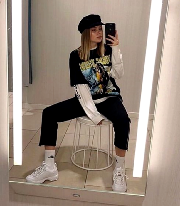 chica rubia usando un sombrero, camiseta oversized negra, top de manga larga blanco, pantalón negro, tenis blancos