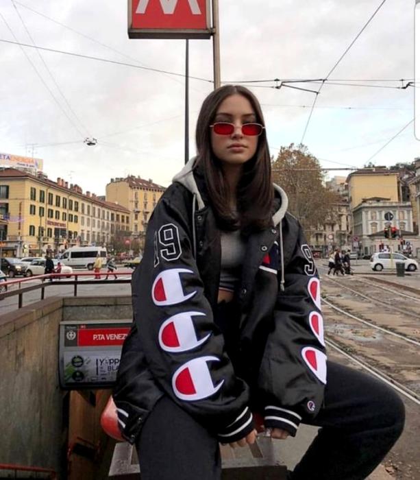 chica de cabello castaño usando lentes de sol rojos, top gris, chamarra negra oversized con logos grandes, mom jeans negros