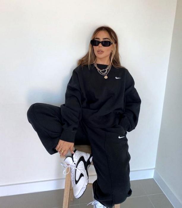 chica de cabello claro usando lentes de sol, sudadera negra oversized, pants negros, tenis blancos