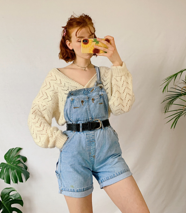 redhead girl wearing beige knitted sweater, denim overalls with black belt at the waist