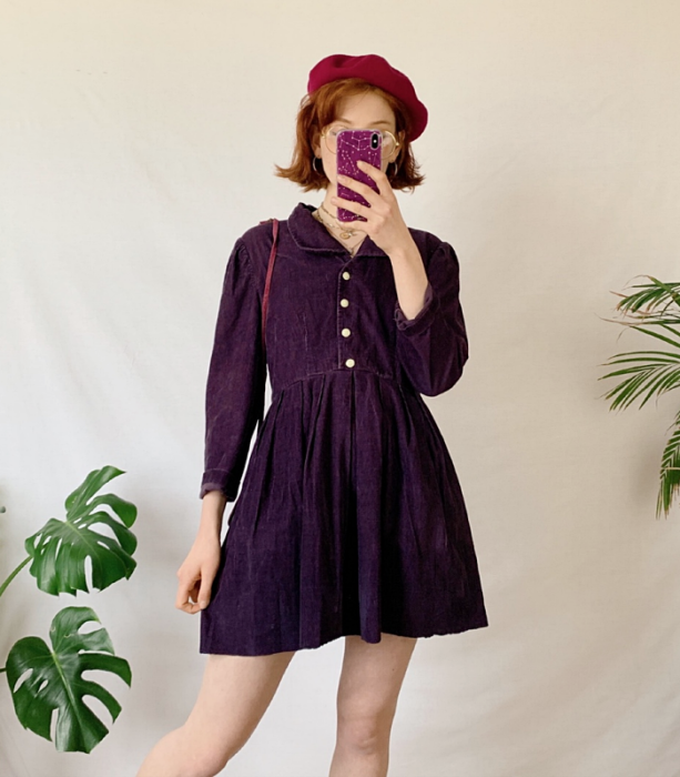 redhead girl wearing purple corduroy dress with button front and collar, pink beret