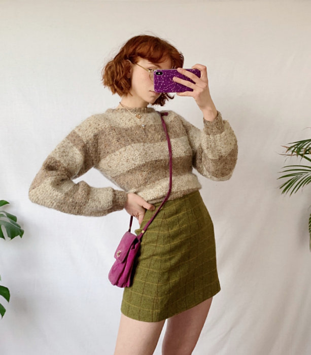 redhead girl wearing beige striped sweater, green plaid mini skirt, fuchsia crossbody bag