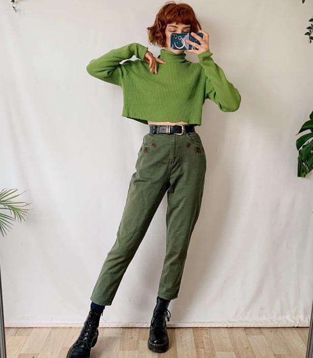 chica pelirroja usando un suéter verde de cuello alto y manga larga, cinturón negro, pantalón a la cintura color verde, botas negras de plataforma gruesa