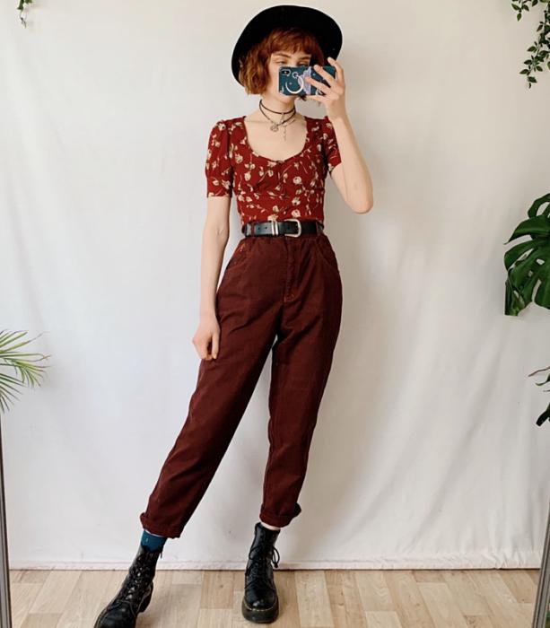 chica pelirroja usando un sombrero negro de ala ancha, top rojo de manga corta y escote redondo, cinturón negro, pantalón de pana guinda, botas de cuero de suela gruesa