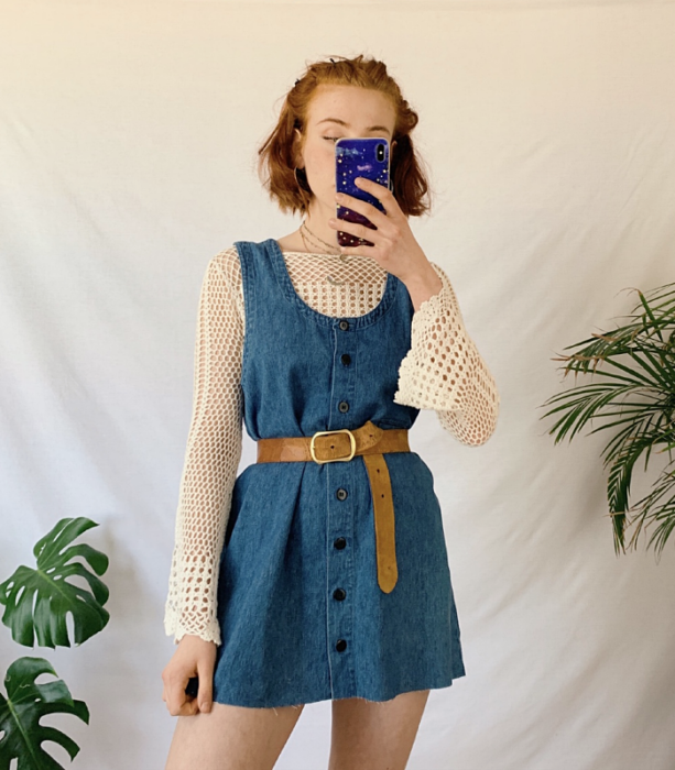 redhead girl wearing beige flared sleeve knit top, button front denim dress, brown leather belt