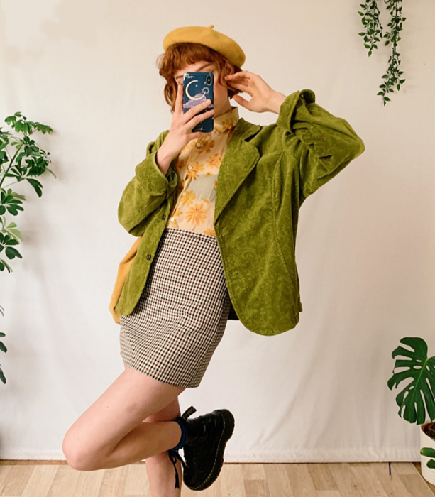 red-haired girl in a yellow beret, yellow shirt with flowers, green velvet coat, beige plaid miniskirt and black thick-soled boots