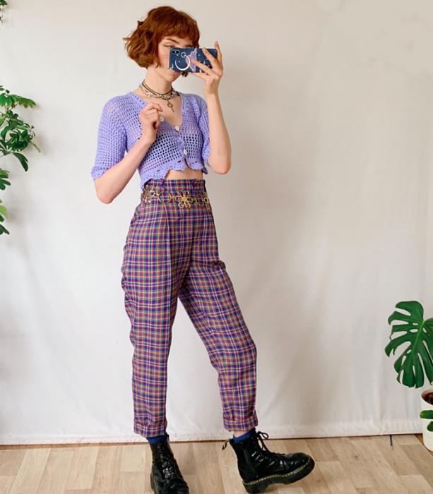 chica pelirroja usando un cárdigan tejido color lavanda, pantalón a la cintura color morado de cuadros, botas negras de suela gruesa