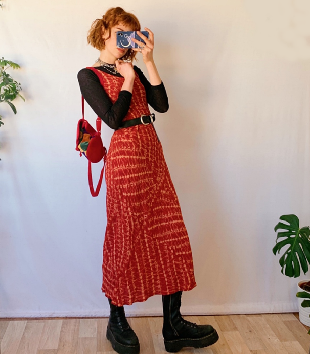 redhead girl wearing long sleeve black top, long red dress with white lines, black belt, black platform boots and red handbag