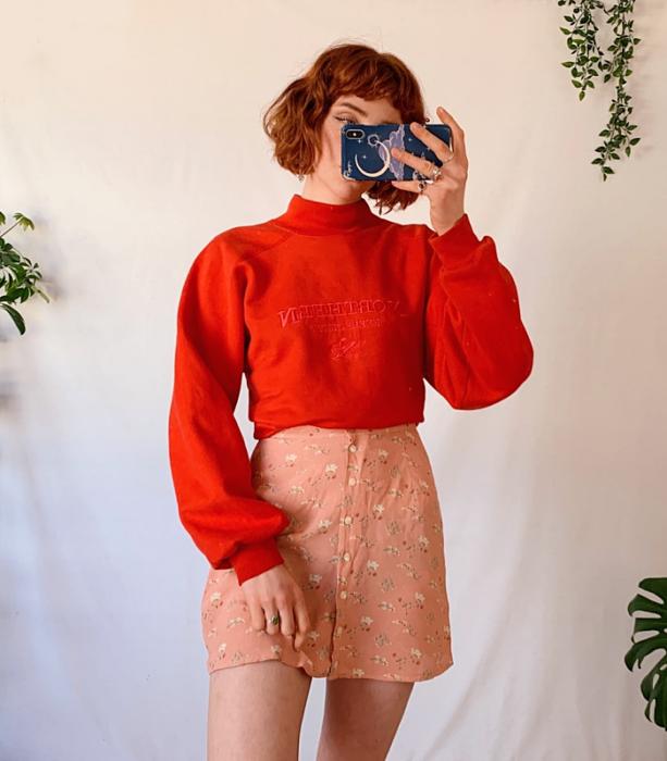 chica pelirroja usando una sudadera roja de cuello alto y manga larga, minifalda rosa con flores blancas