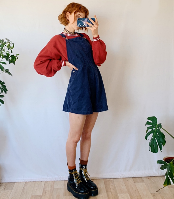 redhead girl wearing red sweatshirt, blue denim overalls dress and black platform boots