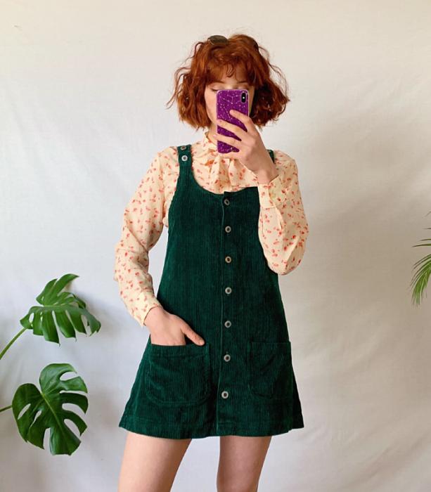 chica pelirroja usando un vestido verde de pana estilo overol, blusa beige de manga larga con estampado de flores rosas
