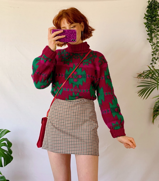 redhead girl wearing fuchsia pink and green print high neck long sleeve sweater, beige plaid mini skirt and pink crossbody bag
