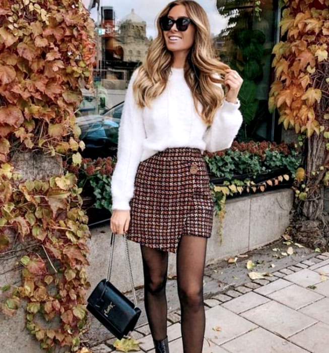 blonde girl wearing white plush sweater, plaid mini skirt with semitransparent black tights and black leather handbag