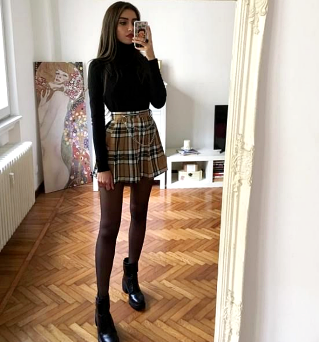 brown haired girl wearing black long sleeve high neck top, yellow plaid plaid mini skirt, semitransparent black tights, black heeled ankle boots