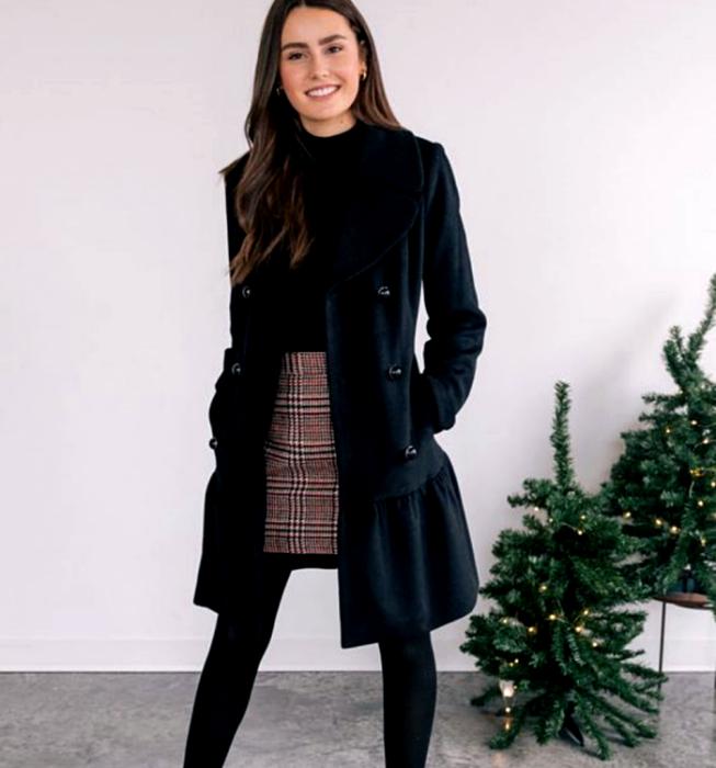 chica de cabello castaño largo usando un top negro, abrigo largo azul marino, minifalda gris de cuadros estilo escocesa, medias negras gruesas